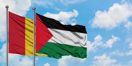 Guinea and Palestine flag waving in the wind against white cloudy blue sky together. Diplomacy concept, international relations. Stock Photo