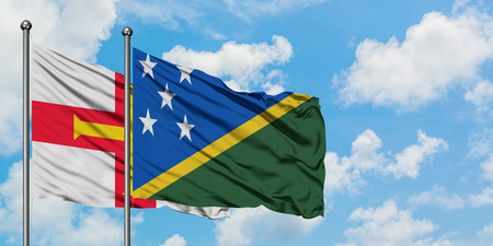 Guernsey and Solomon Islands flag waving in the wind against white cloudy blue sky together. Diplomacy concept, international relations. Stok Fotoğraf