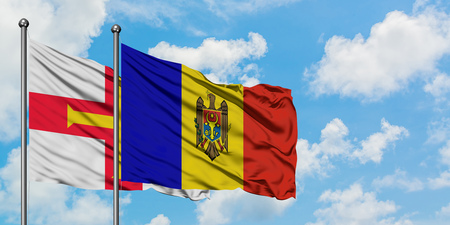 Guernsey and Moldova flag waving in the wind against white cloudy blue sky together. Diplomacy concept, international relations.