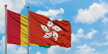 Guinea and Hong Kong flag waving in the wind against white cloudy blue sky together. Diplomacy concept, international relations.