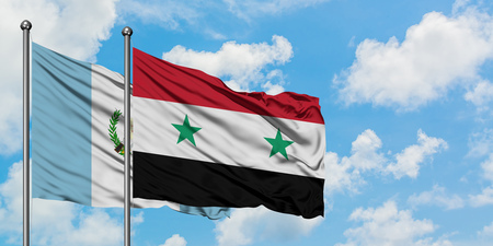 Guatemala and Syria flag waving in the wind against white cloudy blue sky together. Diplomacy concept, international relations.