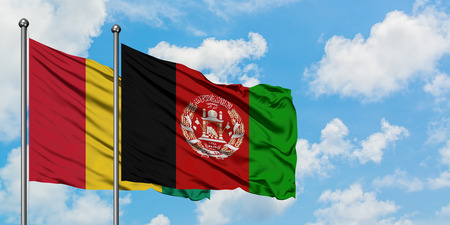 Guinea and Afghanistan flag waving in the wind against white cloudy blue sky together. Diplomacy concept, international relations.