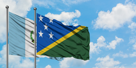 Guatemala and Solomon Islands flag waving in the wind against white cloudy blue sky together. Diplomacy concept, international relations. Stok Fotoğraf