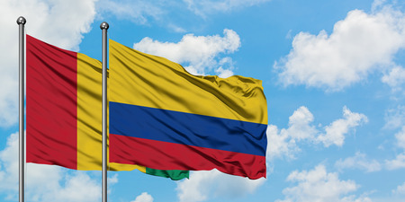 Guinea and Colombia flag waving in the wind against white cloudy blue sky together. Diplomacy concept, international relations.