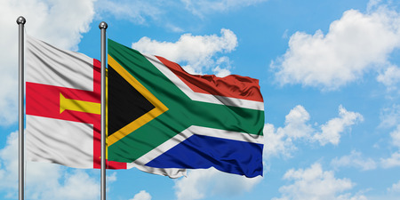 Guernsey and South Africa flag waving in the wind against white cloudy blue sky together. Diplomacy concept, international relations.