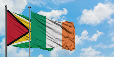 Guyana and Ireland flag waving in the wind against white cloudy blue sky together. Diplomacy concept, international relations.