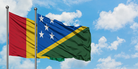 Guinea and Solomon Islands flag waving in the wind against white cloudy blue sky together. Diplomacy concept, international relations.
