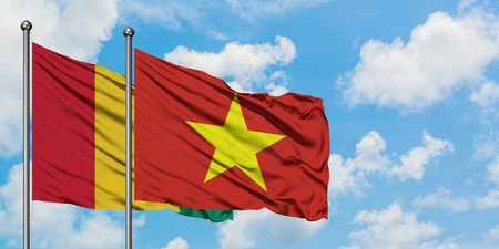 Guinea and Vietnam flag waving in the wind against white cloudy blue sky together. Diplomacy concept, international relations.