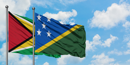 Guyana and Solomon Islands flag waving in the wind against white cloudy blue sky together. Diplomacy concept, international relations. Stok Fotoğraf
