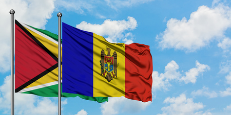 Guyana and Moldova flag waving in the wind against white cloudy blue sky together. Diplomacy concept, international relations.