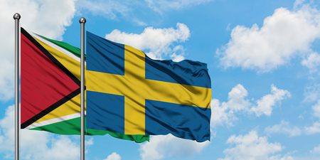 Guyana and Sweden flag waving in the wind against white cloudy blue sky together. Diplomacy concept, international relations.