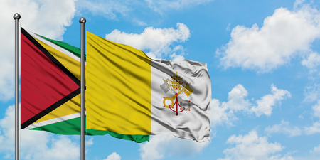 Guyana and Vatican City flag waving in the wind against white cloudy blue sky together. Diplomacy concept, international relations.