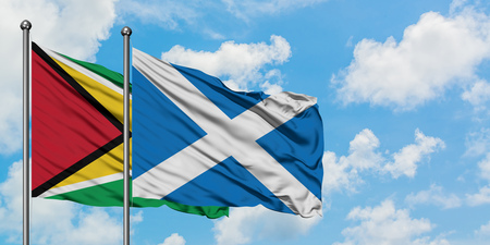 Guyana and Scotland flag waving in the wind against white cloudy blue sky together. Diplomacy concept, international relations.