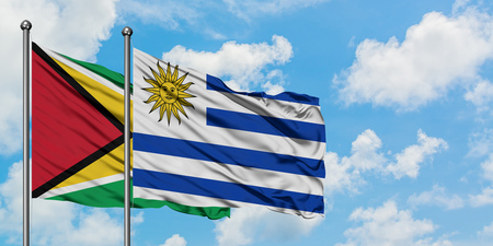 Guyana and Uruguay flag waving in the wind against white cloudy blue sky together. Diplomacy concept, international relations.