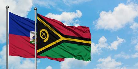 Haiti and Vanuatu flag waving in the wind against white cloudy blue sky together. Diplomacy concept, international relations.