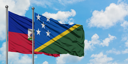 Haiti and Solomon Islands flag waving in the wind against white cloudy blue sky together. Diplomacy concept, international relations.
