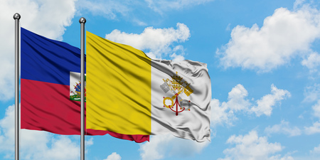 Haiti and Vatican City flag waving in the wind against white cloudy blue sky together. Diplomacy concept, international relations.