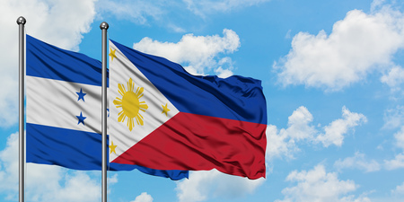 Honduras and Philippines flag waving in the wind against white cloudy blue sky together. Diplomacy concept, international relations.