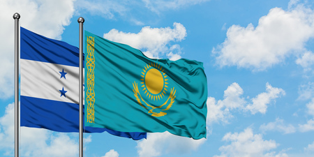 Honduras and Kazakhstan flag waving in the wind against white cloudy blue sky together. Diplomacy concept, international relations. 免版税图像