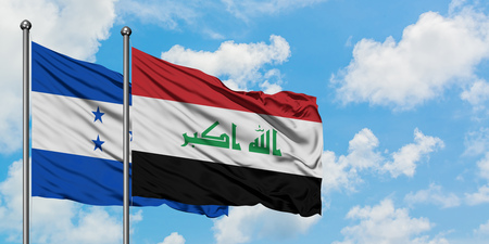 Honduras and Iraq flag waving in the wind against white cloudy blue sky together. Diplomacy concept, international relations.