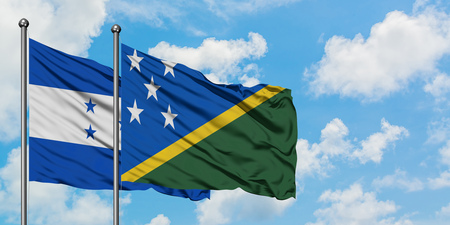 Honduras and Solomon Islands flag waving in the wind against white cloudy blue sky together. Diplomacy concept, international relations. Stok Fotoğraf