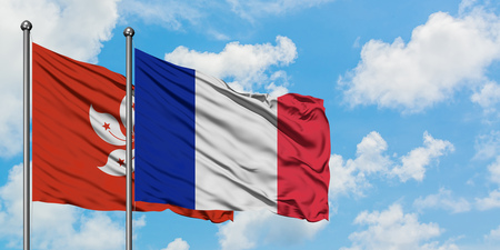 Hong Kong and France flag waving in the wind against white cloudy blue sky together. Diplomacy concept, international relations.