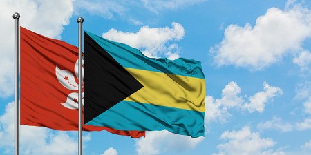 Hong Kong and Bahamas flag waving in the wind against white cloudy blue sky together. Diplomacy concept, international relations. Stock Photo - 123651235