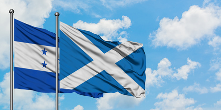Honduras and Scotland flag waving in the wind against white cloudy blue sky together. Diplomacy concept, international relations.