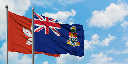Hong Kong and Cayman Islands flag waving in the wind against white cloudy blue sky together. Diplomacy concept, international relations.