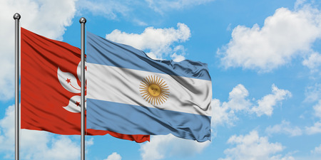 Hong Kong and Argentina flag waving in the wind against white cloudy blue sky together. Diplomacy concept, international relations. Stock Photo