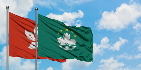 Hong Kong and Macao flag waving in the wind against white cloudy blue sky together. Diplomacy concept, international relations.