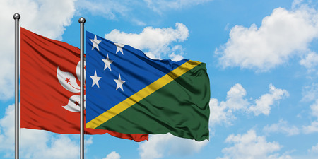Hong Kong and Solomon Islands flag waving in the wind against white cloudy blue sky together. Diplomacy concept, international relations.