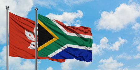 Hong Kong and South Africa flag waving in the wind against white cloudy blue sky together. Diplomacy concept, international relations. 스톡 콘텐츠