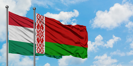 Hungary and Belarus flag waving in the wind against white cloudy blue sky together. Diplomacy concept, international relations.