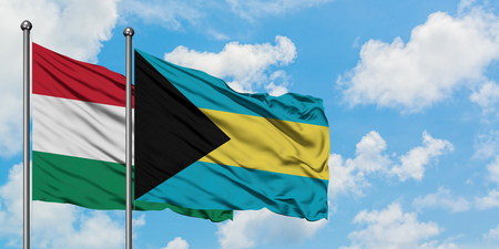 Hungary and Bahamas flag waving in the wind against white cloudy blue sky together. Diplomacy concept, international relations. Stock Photo - 123652651