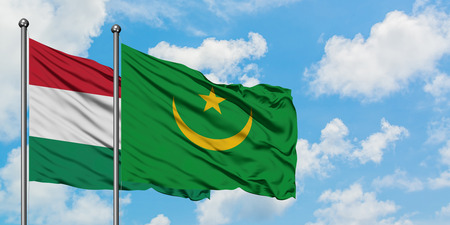 Hungary and Mauritania flag waving in the wind against white cloudy blue sky together. Diplomacy concept, international relations. Фото со стока