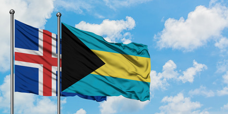 Iceland and Bahamas flag waving in the wind against white cloudy blue sky together. Diplomacy concept, international relations. Stock Photo - 123653122