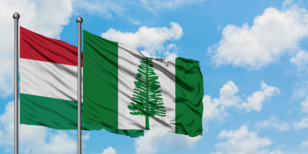 Hungary and Norfolk Island flag waving in the wind against white cloudy blue sky together. Diplomacy concept, international relations. Stock Photo