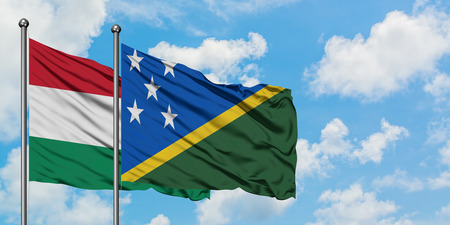 Hungary and Solomon Islands flag waving in the wind against white cloudy blue sky together. Diplomacy concept, international relations.