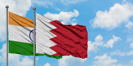 India and Bahrain flag waving in the wind against white cloudy blue sky together. Diplomacy concept, international relations. Stock Photo