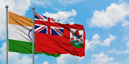 India and Bermuda flag waving in the wind against white cloudy blue sky together. Diplomacy concept, international relations.