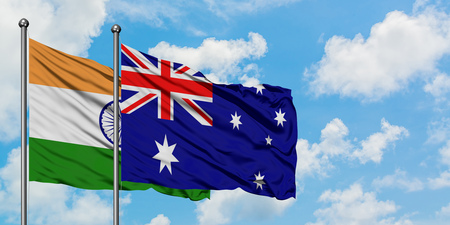 India and Australia flag waving in the wind against white cloudy blue sky together. Diplomacy concept, international relations.