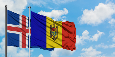 Iceland and Moldova flag waving in the wind against white cloudy blue sky together. Diplomacy concept, international relations. Stock Photo