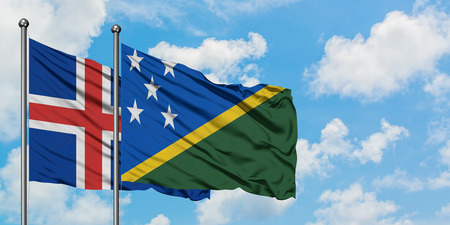 Iceland and Solomon Islands flag waving in the wind against white cloudy blue sky together. Diplomacy concept, international relations.
