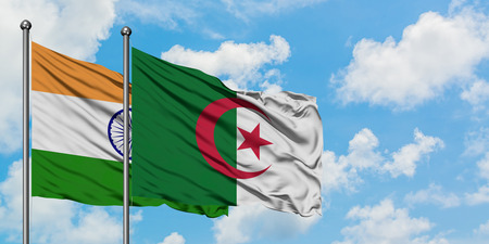 India and Algeria flag waving in the wind against white cloudy blue sky together. Diplomacy concept, international relations.