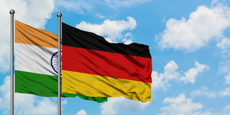 India and Germany flag waving in the wind against white cloudy blue sky together. Diplomacy concept, international relations.