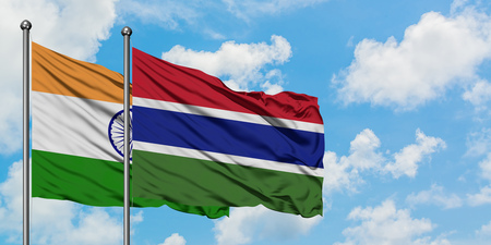 India and Gambia flag waving in the wind against white cloudy blue sky together. Diplomacy concept, international relations.