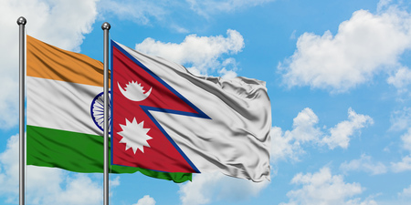 India and Nepal flag waving in the wind against white cloudy blue sky together. Diplomacy concept, international relations.