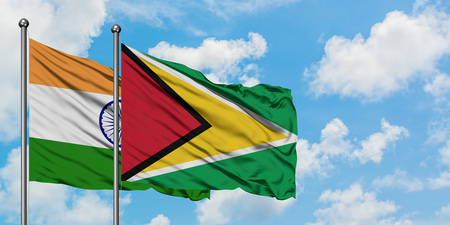India and Guyana flag waving in the wind against white cloudy blue sky together. Diplomacy concept, international relations. 스톡 콘텐츠