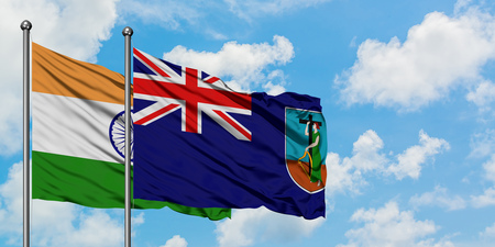 India and Montserrat flag waving in the wind against white cloudy blue sky together. Diplomacy concept, international relations. Stock Photo
